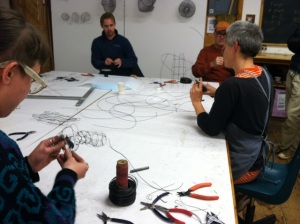Anna Hepler works on woven wire sculptures with attendees, Chris among them
